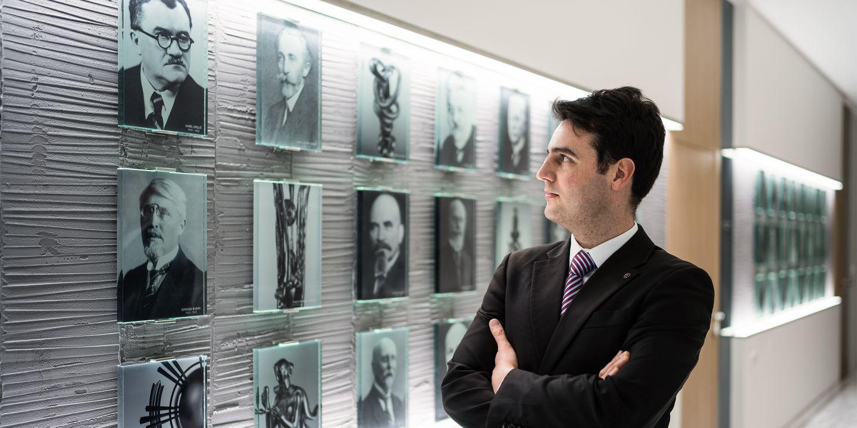 Vít Pokorný před stěnou s fotografiemi rektorů Masarykovy univerzity, která je umístěná na rektorátu. Jeho prapraděda Karel Engliš je na fotografii vlevo nahoře.