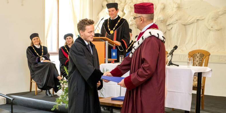 David Kosař z Právnické fakulty MU přebírá dekret od rektora Mikuláše Beka.
