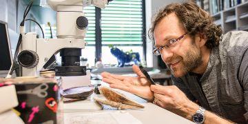 """Biolog Michal Horsák ukazuje na své dlani """"gigantické"""" plže, kteří v Brně žili v době ledové a dnes jsou stále k vidění v Altaji."""