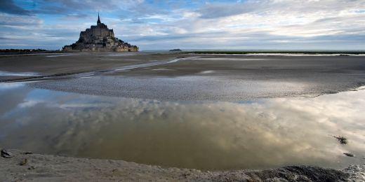Francouzský poloostrov Mont-Saint-Michel je v době přílivu obklopen vodou a za odlivu písky.