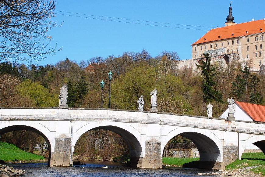Zámek vNáměšti sproslulým barokním mostem vpopředí.