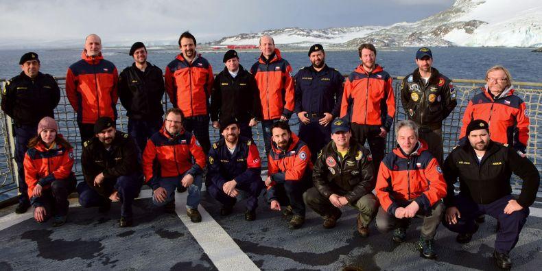 Členové vědecké expedice Masarykovy univerzity na palubě lodi AP-41 Aquiles společně s kapitánem Jorge Ibarrou, piloty vrtulníků a dalšími důstojníky. V pozadí chilská antarktická stanice Arturo Prat.