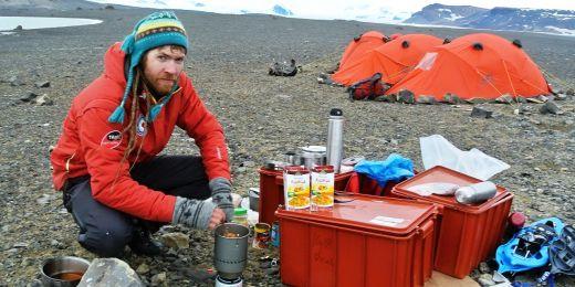Chemik Ondřej Zvěřina připravuje v terénním kempu u jezera Monolith večeři. V pozadí nové expediční stany.