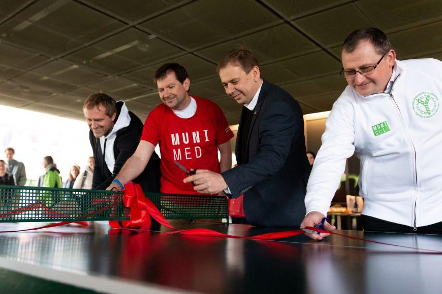 Představitelé univerzity společně otevírají nové stoly na stolní tenis.