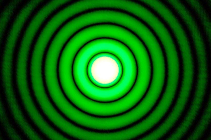 Skvrna na stěně za překážkou smalým otvorem osvětleným laserovým paprskem je mnohem větší než samotný otvor, protože světlo se díky Huygensovu principu odchyluje zpřímého směru.
