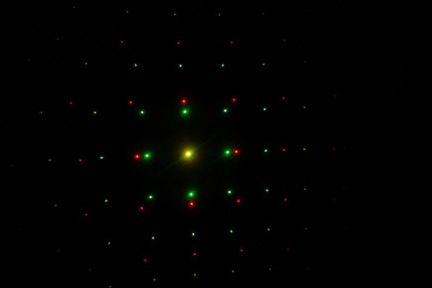 Difrakční obrazec za hustou mřížkou osvětlenou dvěma lasery. Červené světlo má větší vlnovou délku, aodchyluje se proto více než světlo zelené.