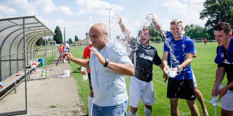 Radost hráčů Muni po vítězství ve fotbalovém turnaji na Českých akademických hrách. Vodou postříkali svého trenéra Karla Večeřu.