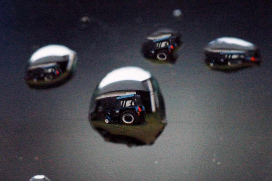 Kapky na skle auta (fotografováno zevnitř) avnich zobrazený traktor (snímek jsme pro lepší přehlednost otočili).