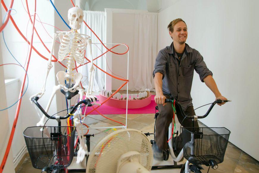 Architekt výstavy Milan Šuška předvádí originální exponát kostry na jízdním kole.