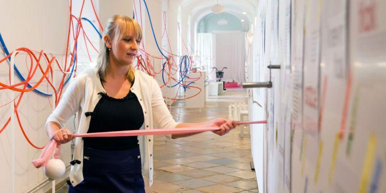 Autorka výstavy Zuzana Hanzelková tahá za růžovou stužku, která demonstruje délku lidských střev.