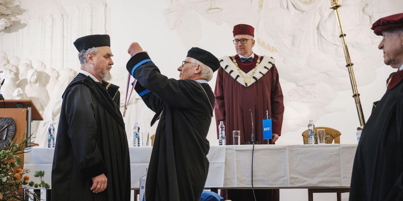 Andrej Zubov (vlevo) přebírá čestný doktorát z rukou prorektora pro výzkum Petra Dvořáka. Vpravo stojí rektor Mikuláš Bek.