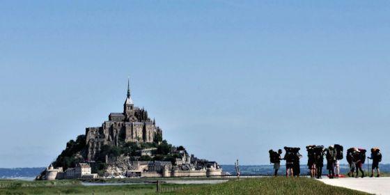 Poutníci před Mont Saint-Michel v Normandii.